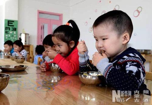 苏嘎日(右)在幼儿园和小朋友一起吃午餐。