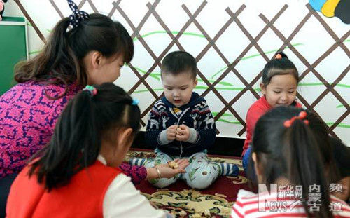 苏嘎日与幼儿园老师和小朋友一起玩羊拐。