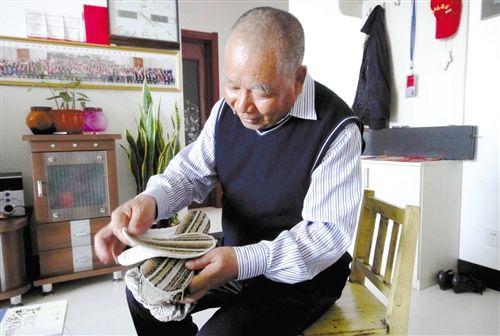 朱清章拿着老母亲亲手缝的鞋垫