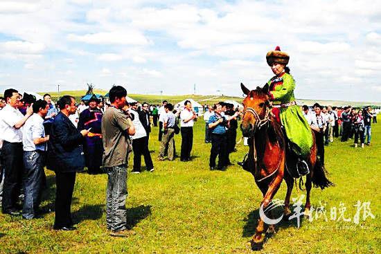 一位牧民骑马从游客身旁走过 (贾立君摄)