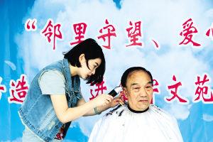 大学东路街道金宇文苑社区一家理发店的造型师正在为一位社区居民理发