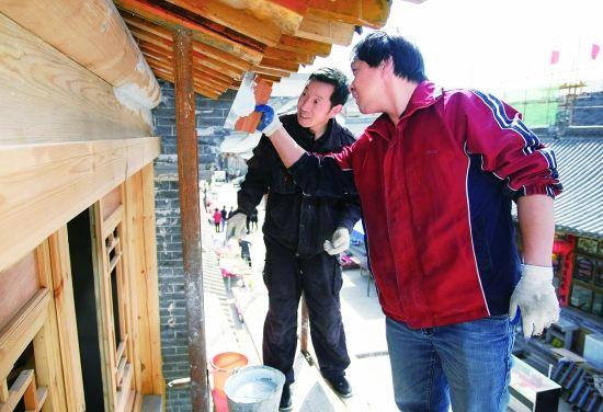 工人们正在粉刷塞上老街里的建筑