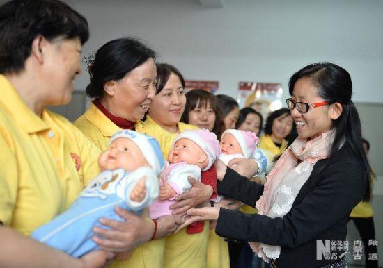 老师在教参加月嫂培训的妇女怎样抱小宝宝