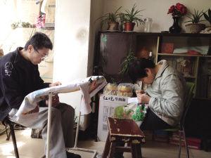 姐弟两人坐在家中绣十字绣
