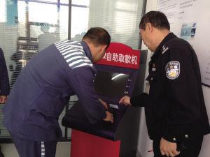 一名服刑人员在学习使用ATM机取款