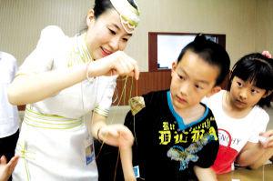 讲解员教孩子们制作五彩粽、五彩缕、五色符