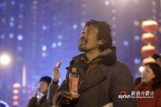 正月十五,郑州CBD,一位流浪汉,在地上捡了半瓶冰红茶,喝了一口,凝视着对面的天空,一朵烟花绽放,他'啪'地一下,微笑了。(田仲煜/图)