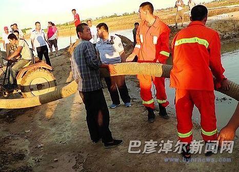 消防官兵和村民一起用抽水泵抽鱼塘里的水