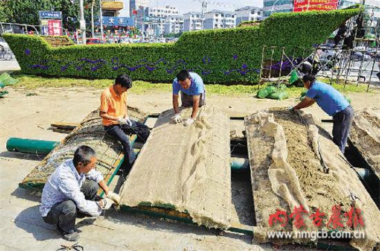 """7月10日,施工人员在昭乌达路与乌兰察布西街十字路口安装主题花坛""""中国梦""""。"""