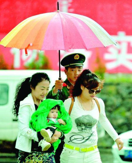 一名边防战士为抱着小孩的游客撑伞遮雨