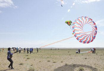 8月19日,一名游客在体验放飞滚地龙风筝。