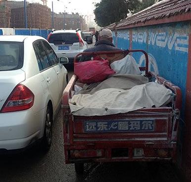 9月27日早,呼和浩特南二环路上一辆电动三轮车被挤得贴住了墙。
