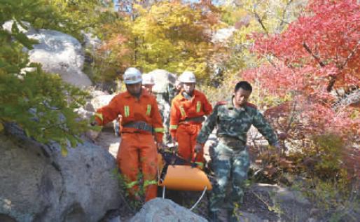 消防官兵抬着伤者下山