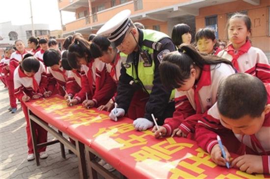 师生与交警共同在条幅上签名