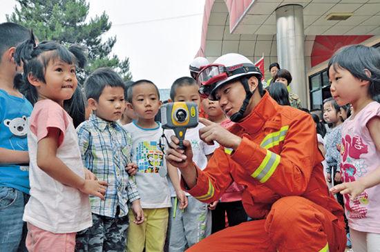 消防员手拿消防救生红外探测仪为孩子们讲解救生知识