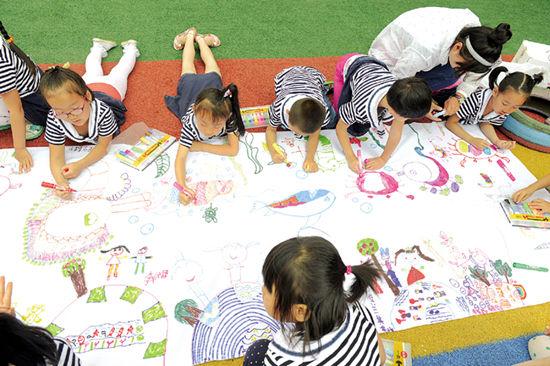 小朋友用画笔在画布上描绘他们心中的美丽家园